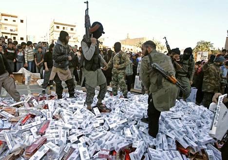 Isisin sotilaita Raqqassa kuvattuna. He ovat juuri takavarikoineet röykkiöittäin tupakkaa sytyttääkseen ne kokoksi.