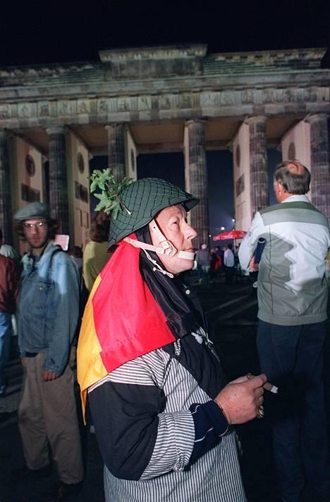Berliiniläinen juhlamies pukeutui itäsaksalaiseen kypärään ja Saksan lippuun 3. lokakuuta 1990, kun Saksa yhdistyi.