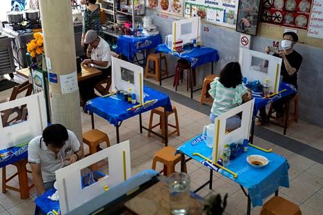 Bangkokilainen nuudeliravintola on ratkaissut asiakkaiden eristämisen pöytiin pystytettyjen muoviseinämien avulla.