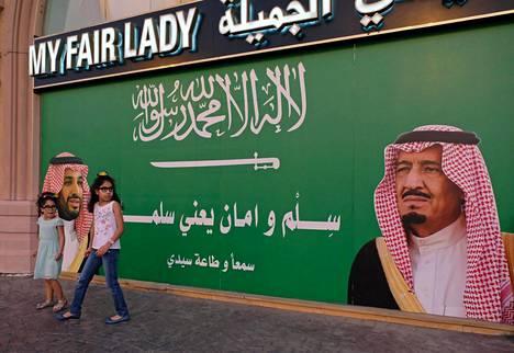 Pikkutytöt leikkivät kuningas Salmania ja kruununprinssi Mohammedia esittävän kuvan edustalla Jeddassa viime perjantaina.