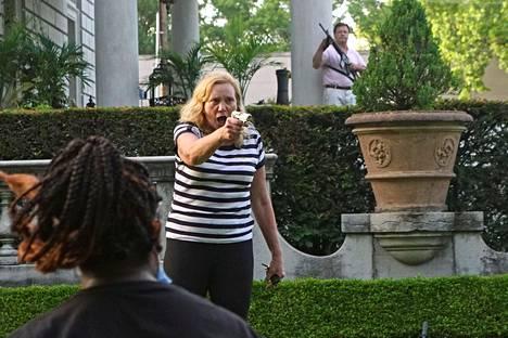 Naisen nähtiin osoittavan useita kertoja mielenosoittajia aseella.