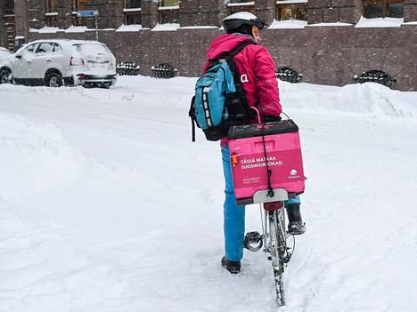 Ruokalähetti polki tammikuussa lumisessa maisemassa Helsingissä.