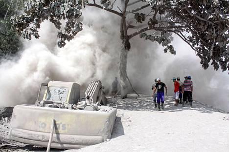 Ihmiset tarkastelevat tulivuoren purkauksen jälkiä.