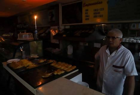 Kauppias työskentelee kynttilänvalossa Buenos Airesissa sunnuntaina.
