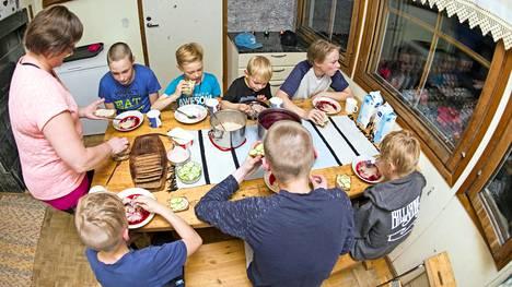 Äiti Eila Savilaakso ja pojat Timo, Tuomas, Eero, Lauri, Juhani, Aapo ja Simeoni iltapalalla.
