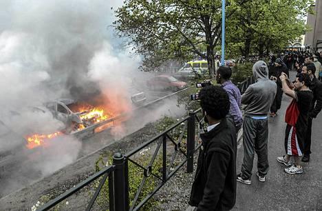 Sivulliset seurasivat, kun joukko autoja paloi Rinkebyn lähiössä Tukholmassa myöhään torstaina.