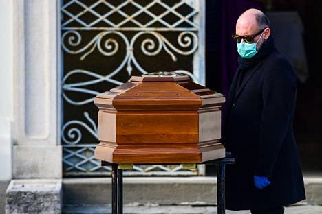 Suojamaskia käyttävä mies osallistui äitinsä hautajaisiin perjantaina Seriatessa Italian Lombardiassa.