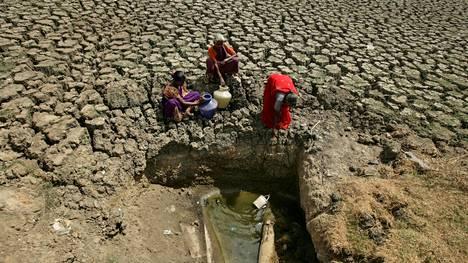 Naiset nostivat vettä kuivuneen vesialtaan pohjalta Chennaissa 11. kesäkuuta.