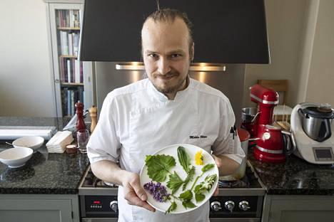 Huippukokki Mikko Utter yhden miehen tilausravintolassaan. Kädessään villiyrtittivalikoima aterian perustaksi.