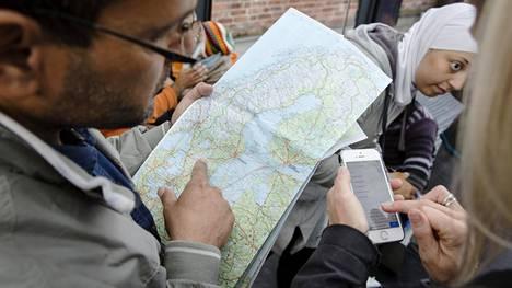 Syyrialaispakolainen katsoo Ruotsin karttaa Malmön rautatieasemalla.