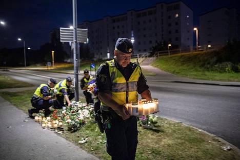 Poliisit siirsivät lukuisat kukat ja kynttilät uudelle muistopaikalle koivun alle.
