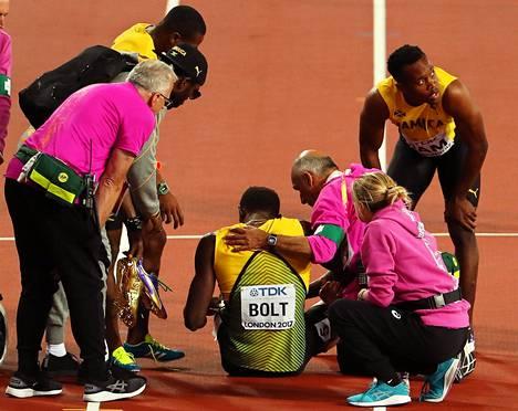 Joukkuetoverit ja lääkintähenkilökunta riensivät auttamaan Usain Boltia.