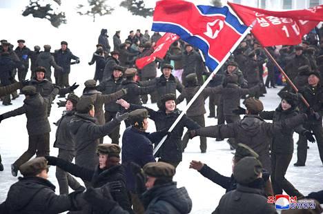 Mustiin talvivaatteisiin pukeutuneet kansalaiset tanssivat lippujen liehuessa.