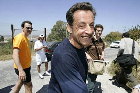 Ranskan tuleva presidentti Nicolas Sarkozy joutui vastailemaan kiusallisiin kysymyksiin kesken jouksulenkkinsä.