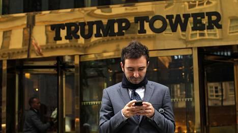 Mies käytti kännykkää Trump Towerin edessä New Yorkissa 2012.