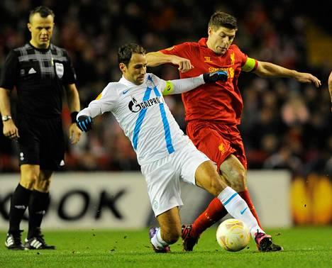 Pietarin Zenitin valkopaitainen Roman Shirokov väänsi pallosta Liverpoolin kipparia Steven Gerrardia (oik.) vastaan Eurooppa-liigan ottelussa talvella 2013.