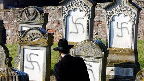 Rabbi Harold Abraham Weill katseli vandalisoituja hautakiviä juutalaisten hautausmaalla Westhoffenissa keskiviikkona.