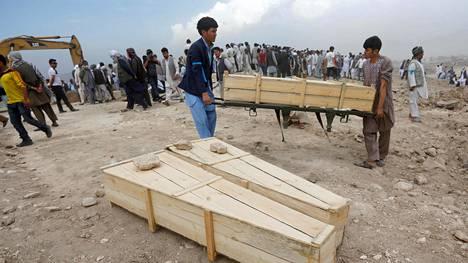 Miehet kantoivat Kabulissa edellisenä päivänä tehdyssä itsemurhaiskussa kuolleille tehtyjä arkkuja sunnuntaina.