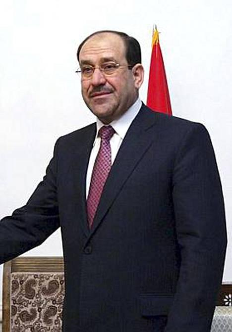 Irakin pääministeri Nuri al-Maliki jakaa rahaa tavallisille ihmisille.