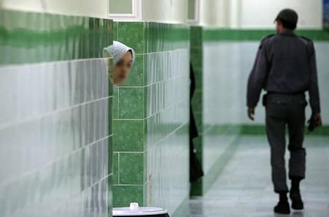 Vanki kurkkaa seinän takaa Evinin vankilassa Teheranissa, kun vartija kulkee ohi.