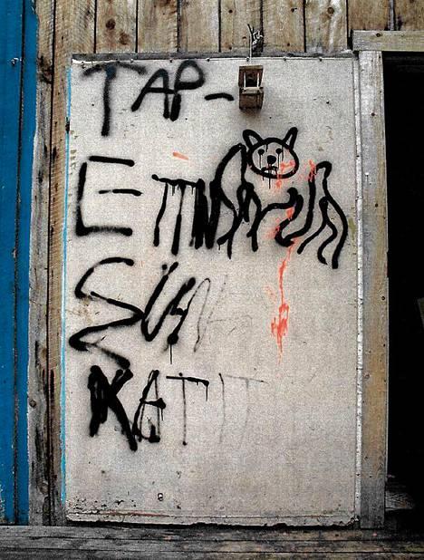 """Mökin ovi oli tahrittu spray-maalilla: """"Tapettiin sun katit""""."""