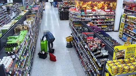 Hyllyltä ottamansa tavarat hän sulloo aiemmin varastamaansa vihreään matkalaukkuun ja vierellä näkyviin kasseihin.