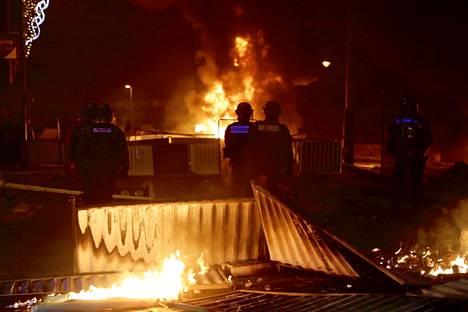 Poliisit vartioivat tuleen sytytettyjen katuesteiden luona Caenissa Normandiassa.