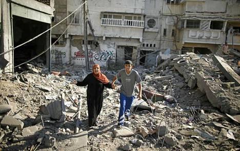 Nainen saapui katsomaan tuhoutunutta kotitaloaan Gazan kaupungissa.