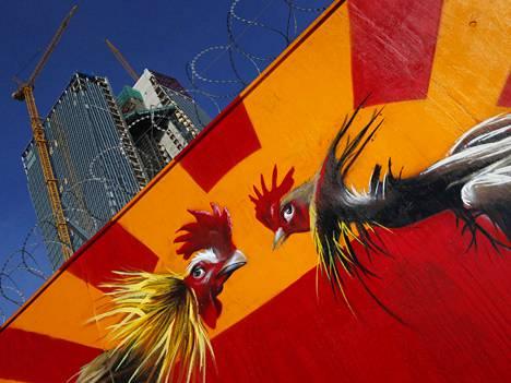 Kukot taistelevat graffitissa, joka on maalattu Euroopan keskuspankin rakennustyömaata kiertävään aitaan.