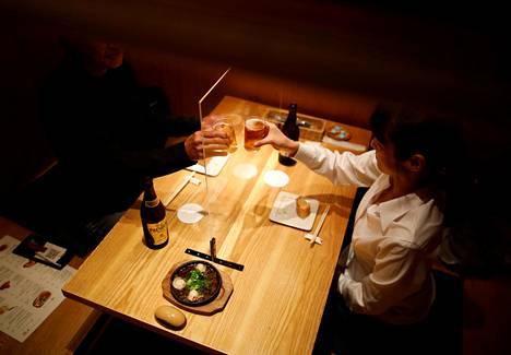 Tokiolaisen Izakaya-pubin asiakkaiden väliin on asetettu läpinäkyvä pleksisuoja.
