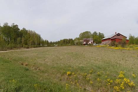 Maantietä ajaessa pellon takaa pilkottaa hetken ajan vaaleanpunainen talo.