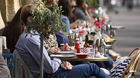 Ihmisiä nauttimassa lämpimästä säästä ravintolan terassilla Helsingissä 3. kesäkuuta 2021.