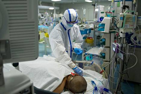 Hoitaja tarkasti potilaan Kiinan Wuhanissa sijaitsevan sairaalan teho-osastolla, jossa hoidetaan koronaviruspotilaita.