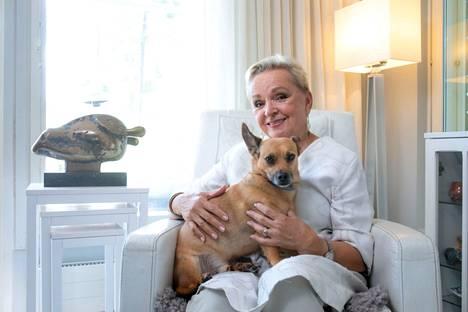 Raija Oranen kotonaan Topi-koiransa kanssa.