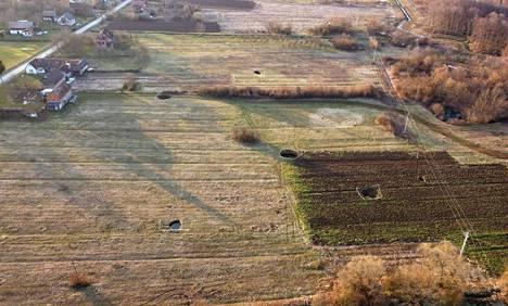 Laajemmassa ilmakuvassa näkyy useita Mecencanin kylän liepeille syntyneitä maanvajoamia.