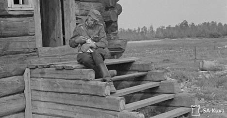 Sotilasvirkailija Stjenberg erään talon portailla kissa sylissä. Kissat ja koirat olivat ainoat elävät olennot kylässä. Ontrosenvaarasta itään 1941.08.15