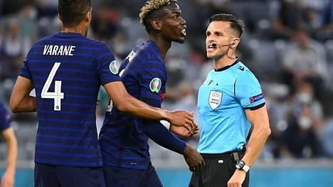 Paul Pogba (kesk.) ja Ranska–Saksa-ottelun erotuomari Carlos Del Cerro Grande (oik.) kävivät tiukkaa keskustelua.