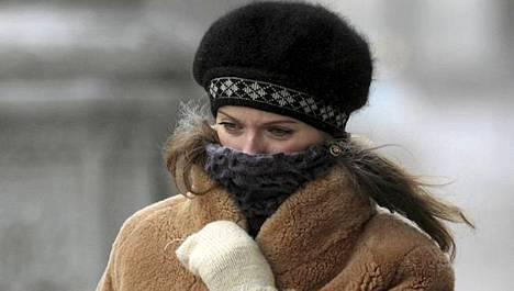 Nainen suojasi kasvojaan pakkaselta Minskissä Valko-Venäjällä torstaina.