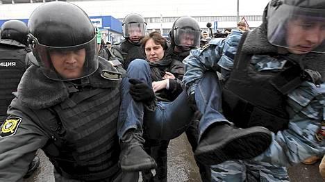 Mellakkapoliisit raahavat pois mielenosoittajaa Moskovassa sunnuntaina.