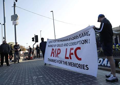 Liverpoolilaisia mielenosoittajia Leedsissä. Monien kannattajien mielestä ahneus ja korruptio ovat pilanneet työläisten pelin, kuten tässäkin bannerissa todetaan.