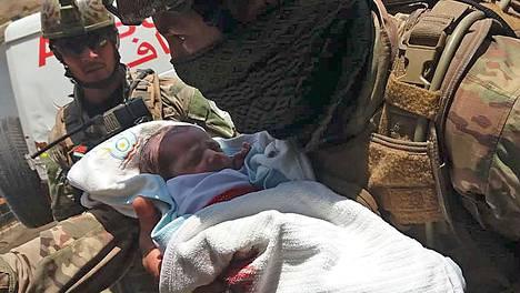 Afganistanin turvallisuusjoukkojen sotilas kantoi Kabulissa sairaalaan tehdystä terrori-iskusta pelastunutta vastasyntynyttä vauvaa.