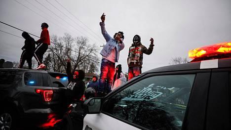 Mielenosoittajat kiipesivät poliisiauton päälle Brooklyn Centerissä Minnesotassa.