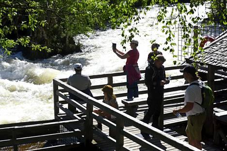 Matkailijoita ihailemassa Myllykosken kuohuja Oulangan kansallispuistossa Kuusamossa.