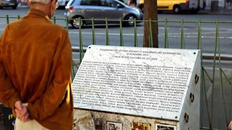 Mies katseli terrori-iskun uhrien kunniaksi pystytettyä muistomerkkiä Bataclanin teatterin lähellä Pariisissa 3. syyskuuta.