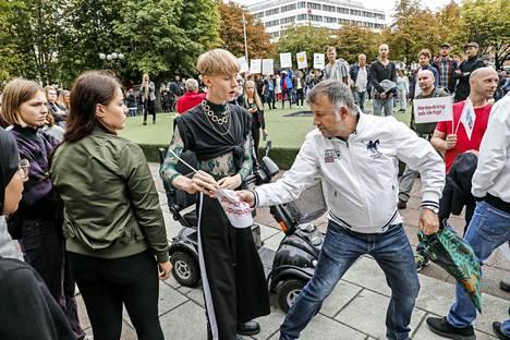 Vaalitilaisuus meni käsirysyksi. Valkotakkinen mies tönäisi rajusti yhden nuorista mielenosoittajista selälleen kivetykselle pian kuvan oton jälkeen.