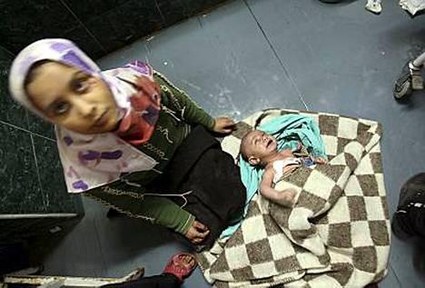 Palestiinalaisnainen istuu israelilaistankin ampumasta kranaatista loukkaantuneen lapsensa vierellä Shifan sairaalassa Gazassa.