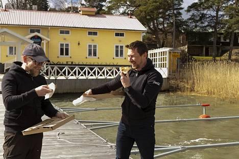 Tuuli meinaa tehdä tepposet, kun Ville Vuorio (vas.) ja Tuomas Levanto maistelevat pitsaa laiturilla.