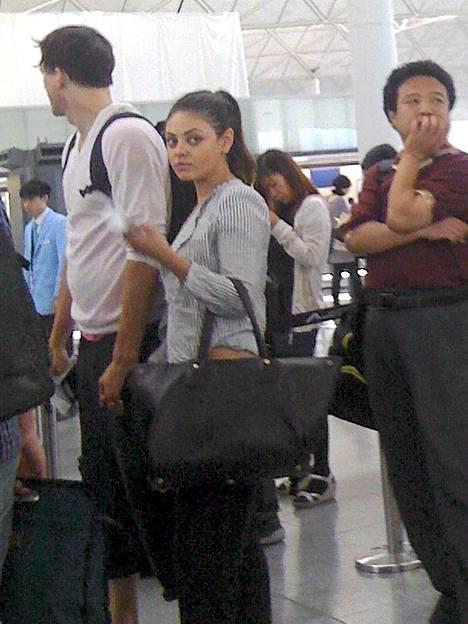 Mila Kunis ja Ashton Kutcher kuvattuna Hong Kongin lentolentällä, kun pari oli matkalla yhteiselle lemmenlomalle Baliin.