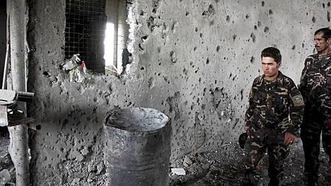 Afganistanin turvallisuusviranomaiset tutkivat rakennusta, joka on luodinreikiä täynnä.