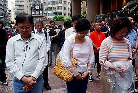 Jalankulkijat hiljentyivät ostoskeskuksessa Hongkongin Times Squarellä muistamaan viikko sitten tapahtuneen maanjäristyksen uhreja.